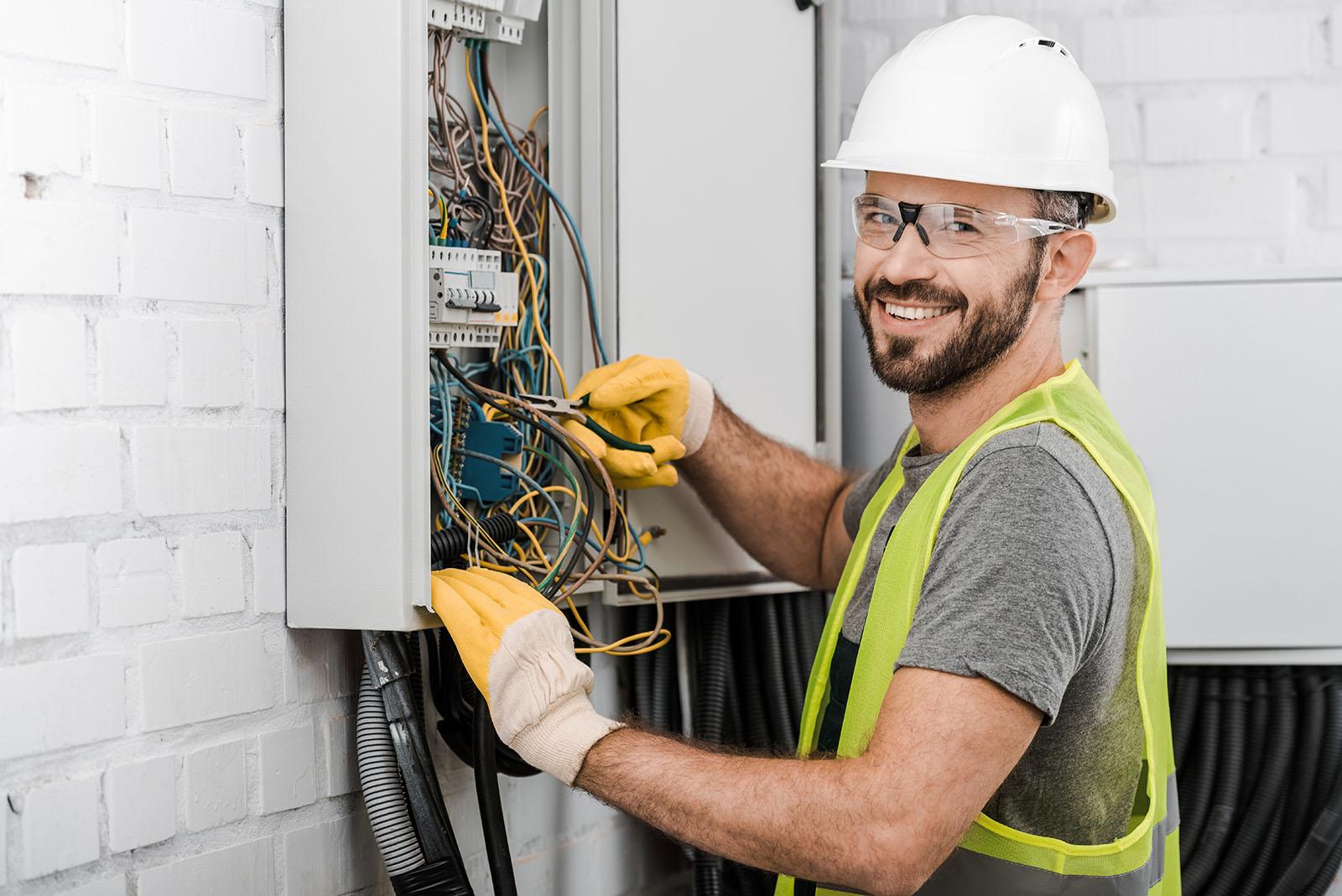 Leende elektriker i vit hjälm arbetar med ett elskåp.