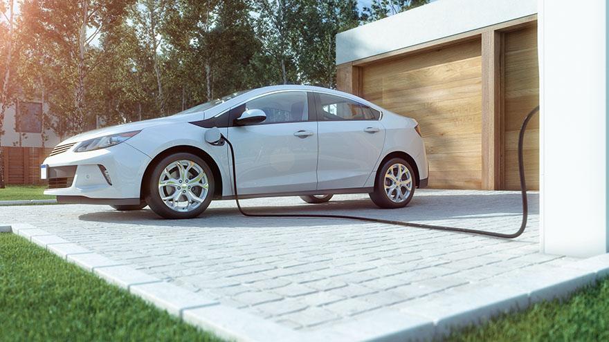 En vit elbil på laddning på en uppfart.