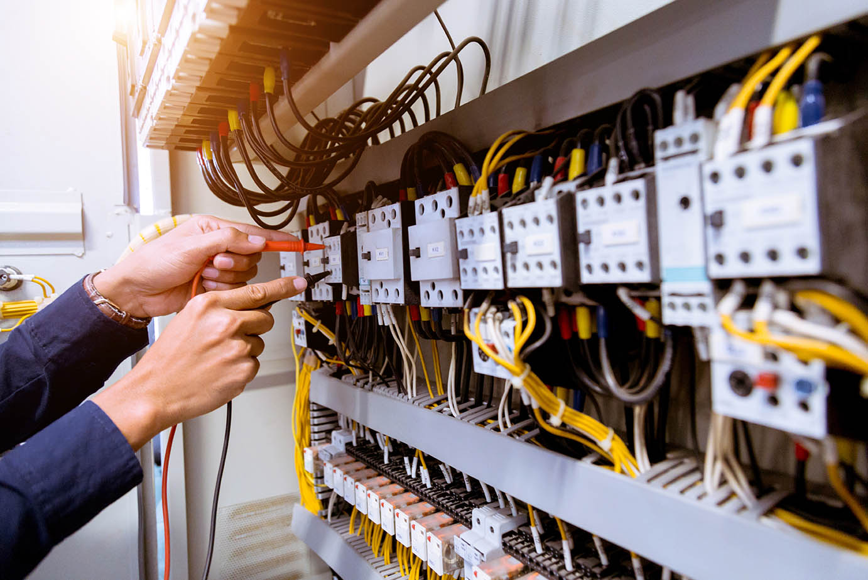 En elektriker mäter strömmen i ett kontrollskåp med en mentometer.
