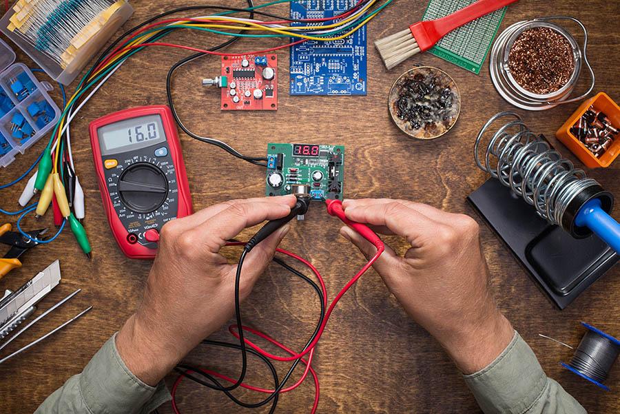 Ett par händer och en yta med mängder av elektriska redskap.