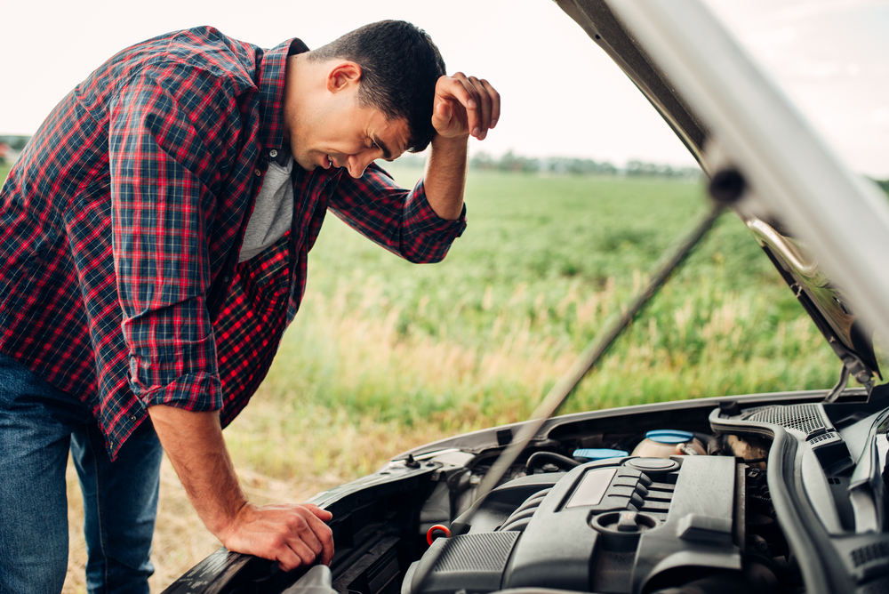 man försöker laga något i motorhuven