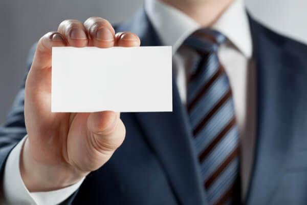 En man i kostym visar upp sin visitkort