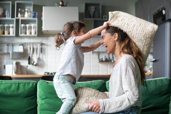 Ett barn kastar kudde på en kvinna