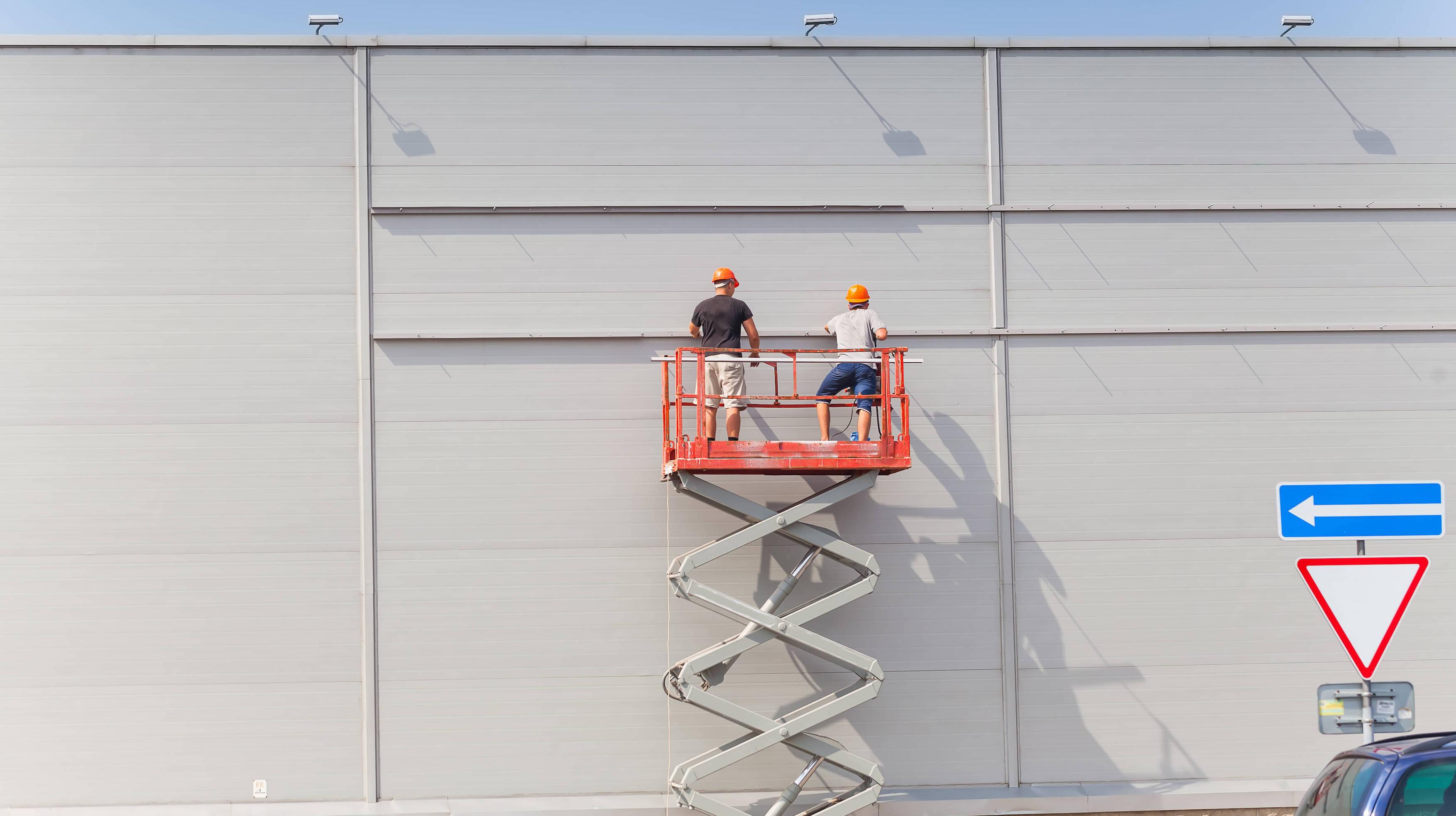 Byggare som jobbar på fasad