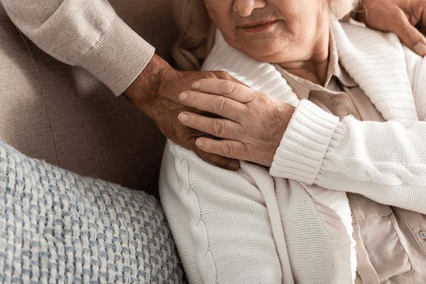 Äldre kvinna håller om handen