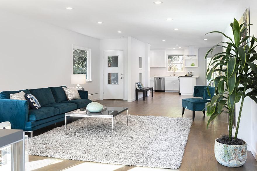 Ljus och modern lägenhet med trägolv inredd med en fluffig matta och designmöbler.