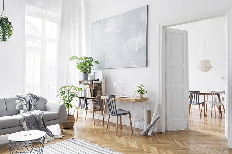 En smakfull ljus lägenhet med parkettgolv, en ljusgrå soffa, en bokhylla i bambu och ett litet skrivbord i trä.