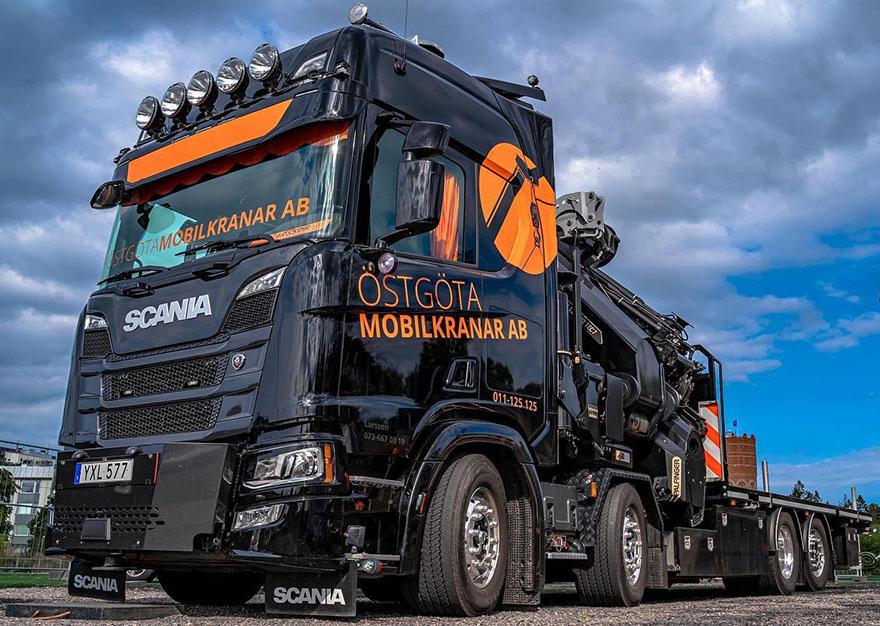 En svart lastbil med orange företagstryck, blå himmel i bakgrunden.
