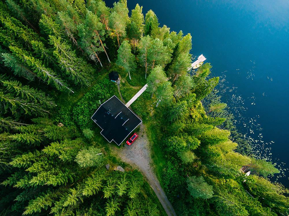 Behöver ni en radonmätning i Gävle? Vi besiktigar, mäter och utreder alla slags hus och fastigheter, här en röd villa i skogen vid en sjö.