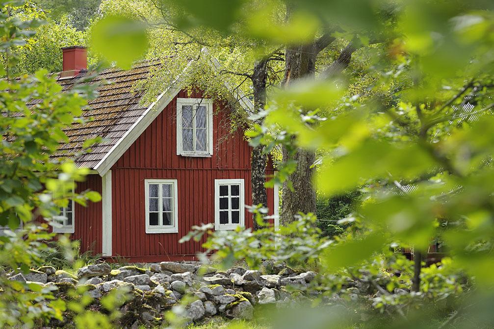 Radon kan finnas överallt, även här i en röd villa; i dess mark, byggnadsmaterial eller vatten. Kontakta oss för radonmätning i Gävle.