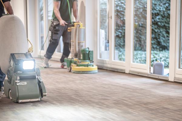 Arbetare slippar golvet med en slipmaskin