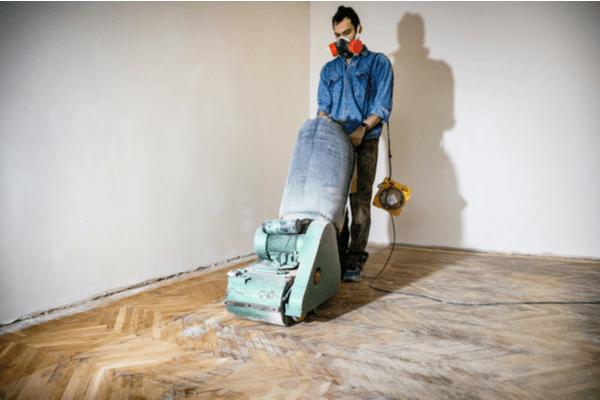 En man slipar golvet med slipmaskin