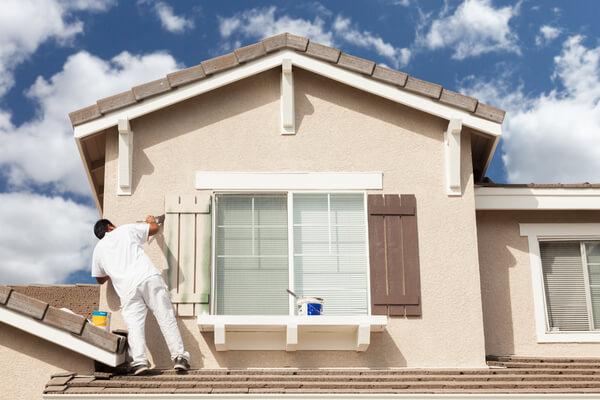 En man målar ett hus