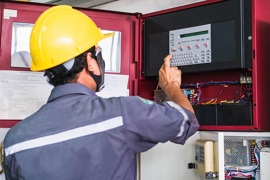 En elektriker i gul hjälm undersöker ett larm.