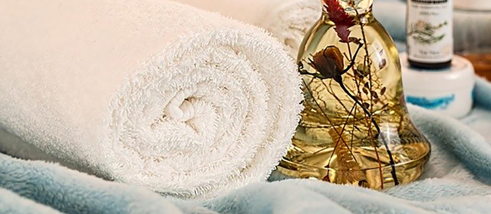 Hemmaspa med handdukar och flaskor med badprodukter.