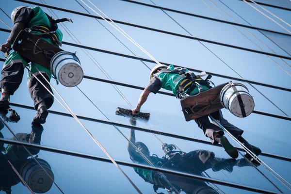 Två män jobbar med fönsterputsning