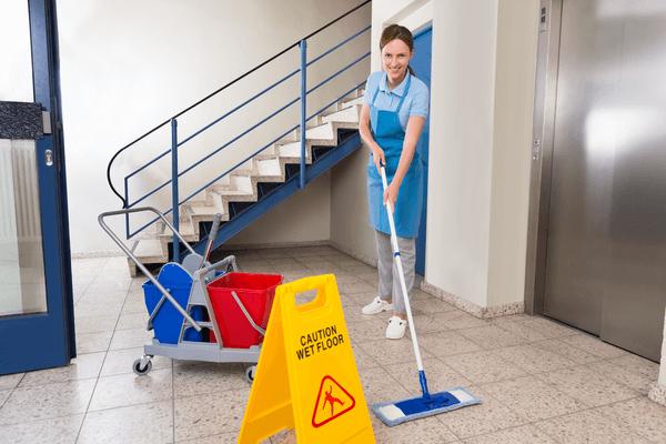 En kvinna moppar golvet i en trapphus