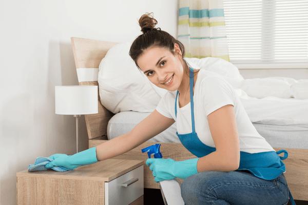 Glad kvinna torkar sängbordet