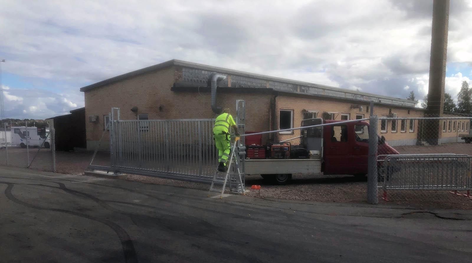 Person i gula arbetskläder står på en stege och jobbar med ett stängsel med grind.