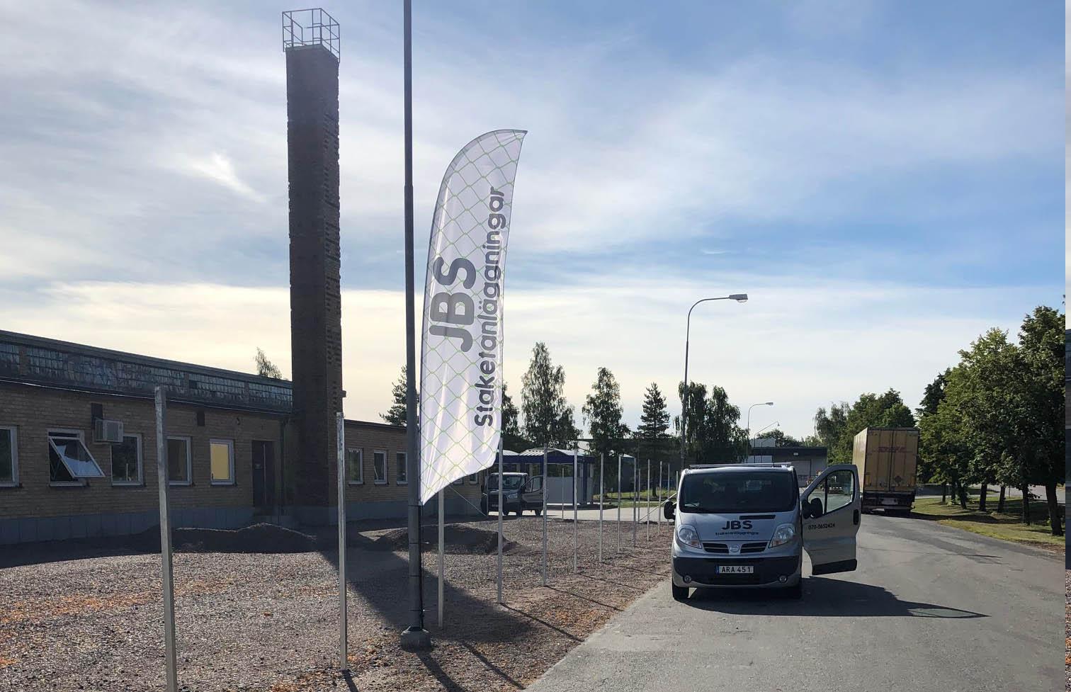 Företagsbil på gata. Till vänster om gatan finns en byggnad, staketstolpar och en flagga med företagsnamnet.