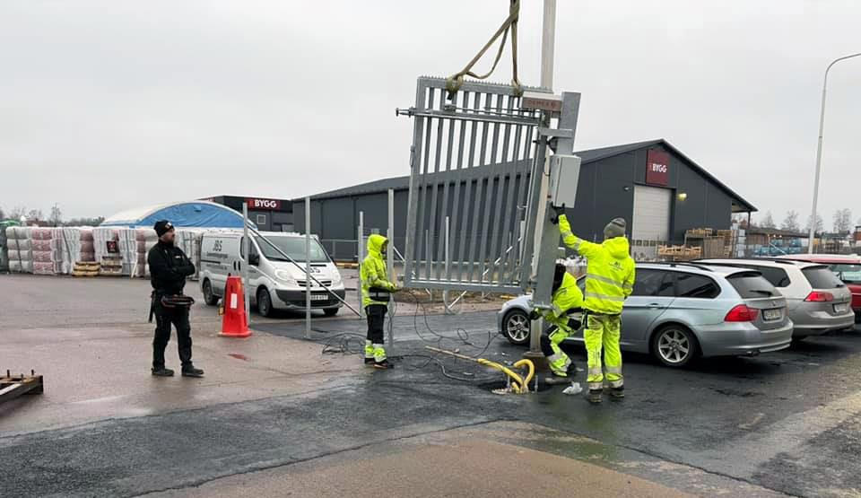 Arbetare i färd med att bygga ett nytt stängsel i Linköping, med grind.