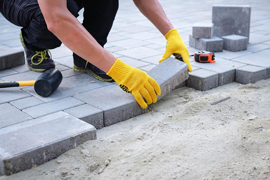En stenläggare i gula handskar lägger grå sten på sandbotten.
