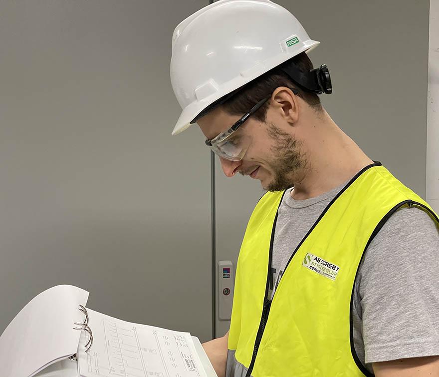 Tekniker i hjälm, gul väst och skyddsglasöhon läser i papper.