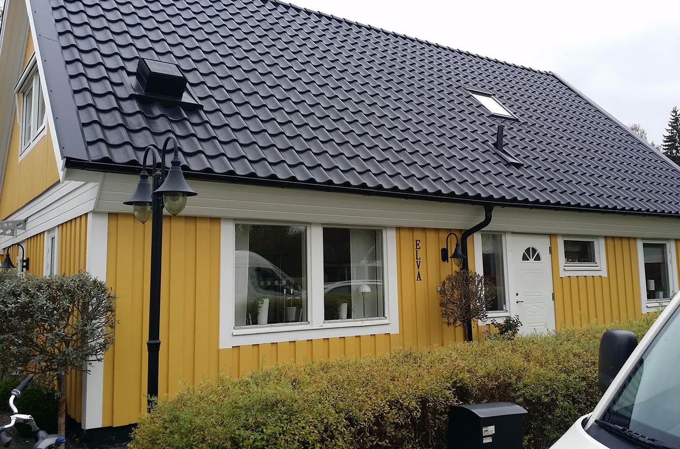 Vi har takläggare i Växjö för alla slags tak. Här är ett svart tak med betongpannor på ett gult hus.