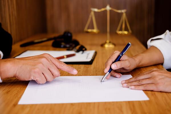 advokat pekar på papper som ska skrivas på