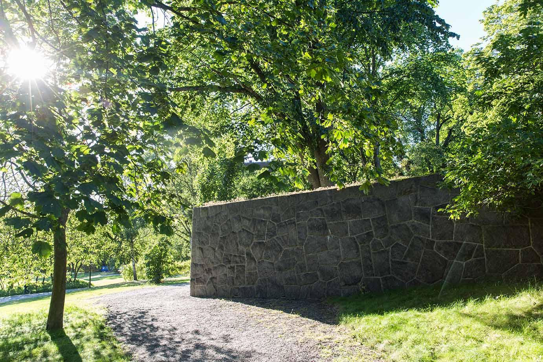 Vi utför olika trädgårdsanläggningar i Stockholm med stenpartier som här en hög mur i en park.