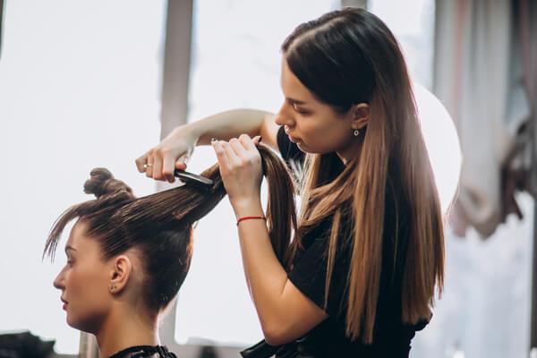 En kvinna klipper håret