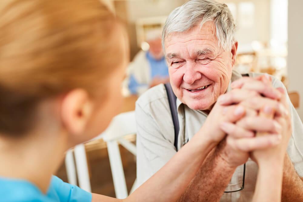 äldre man håller hand med en sköterska